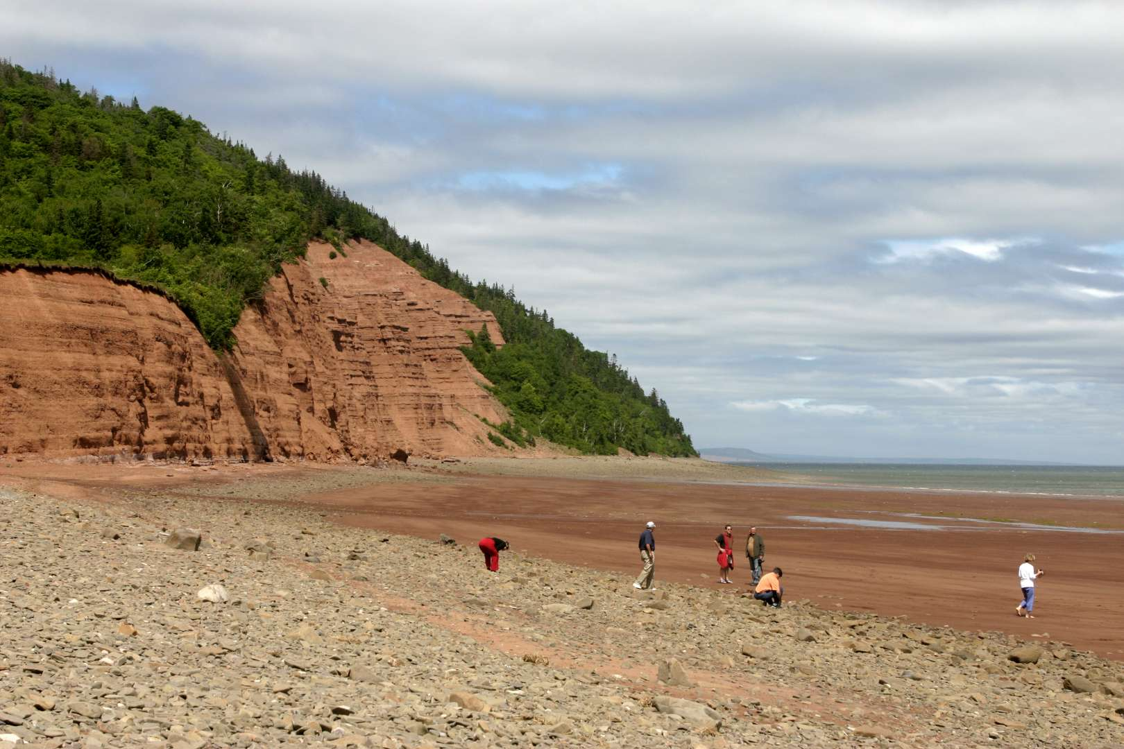 The red hills surrounding Blomidon Beach near Canning Nova Scotia is a favorite spot for people to walk on the beach. The high tides of the Bay of Fundy leave a large sand beach for walking at low Tide. **For Editorial and Personal Use Only