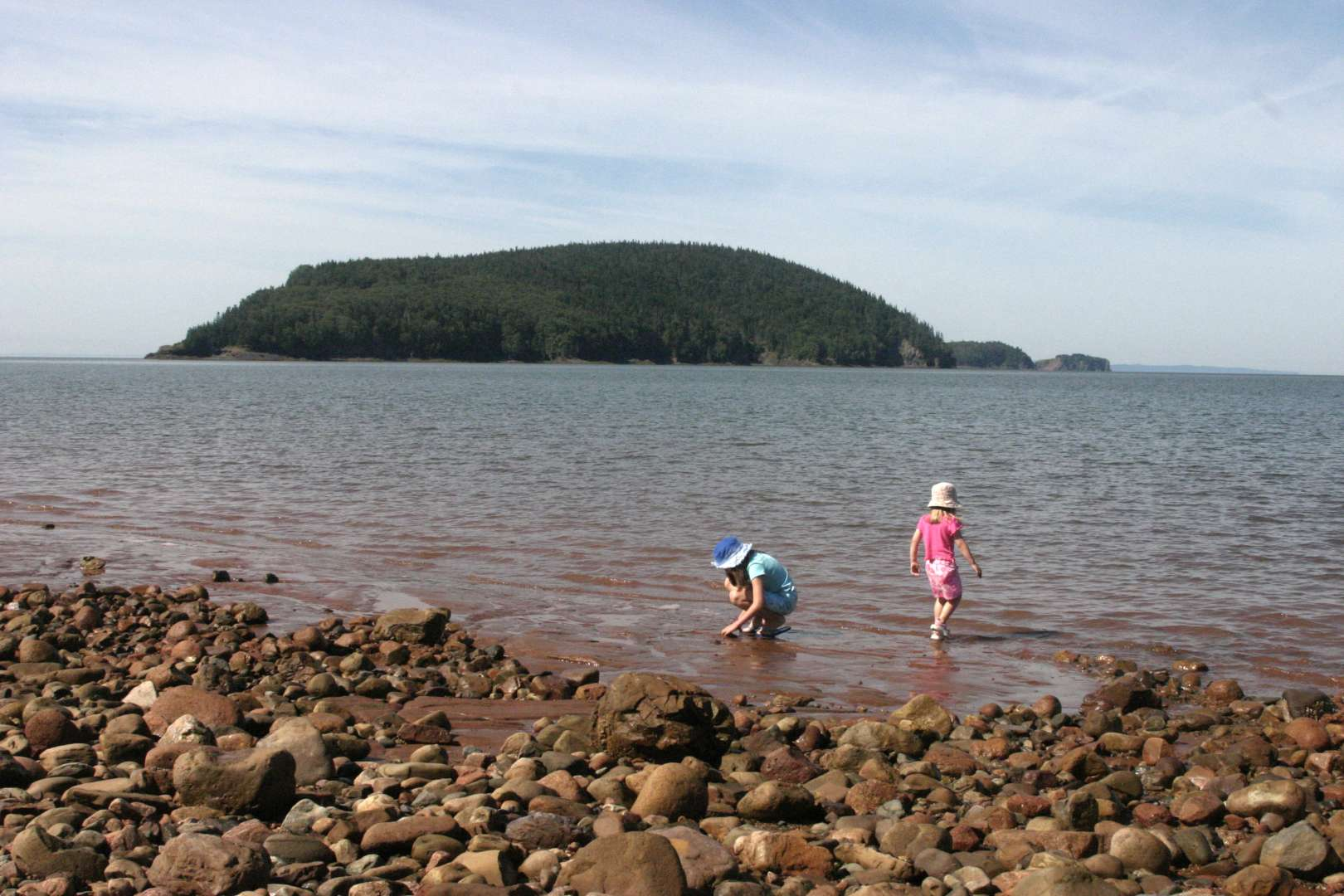 Children play in the tide waters at Five Islands provincial park near Ecomony, Nova Scotia.