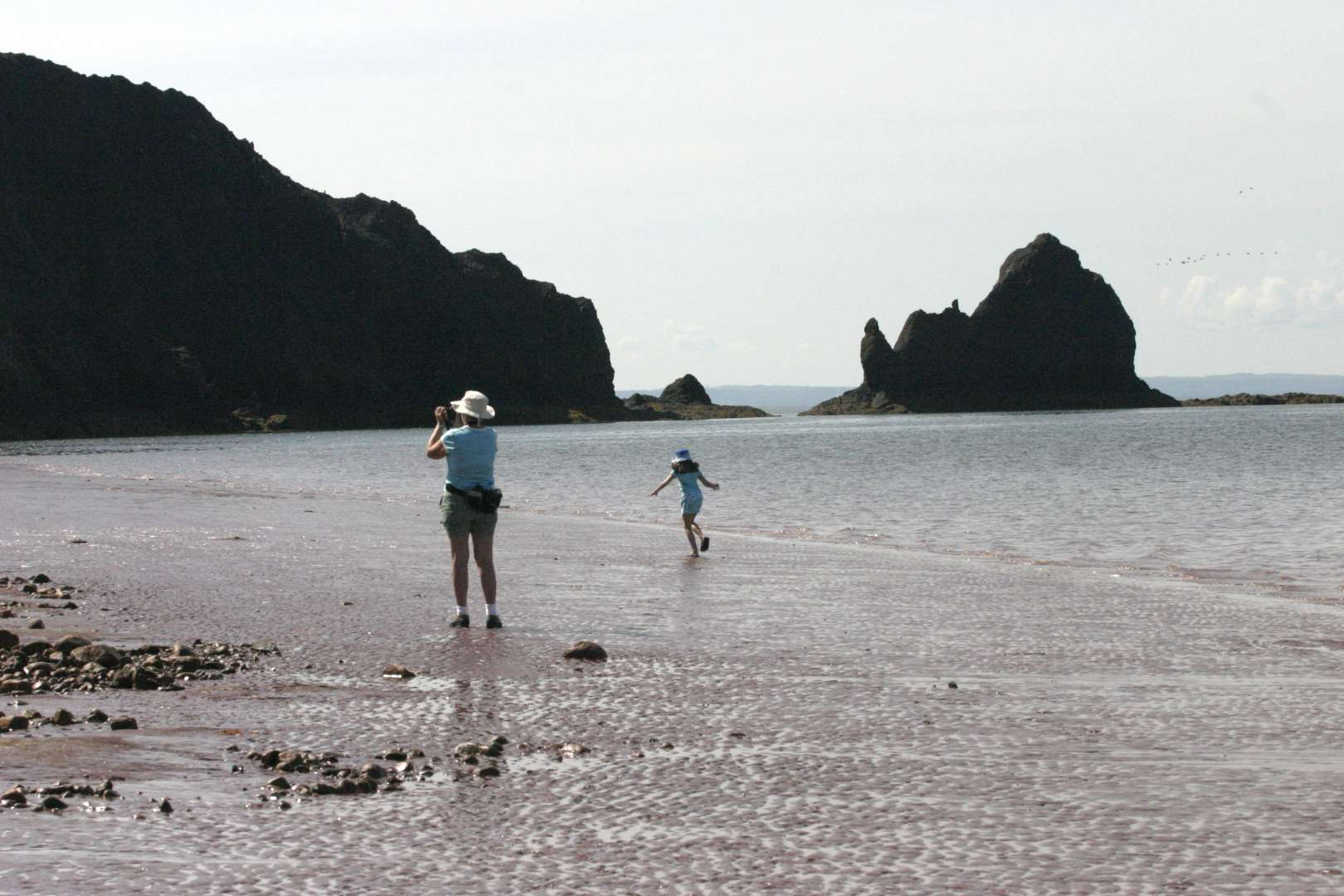 People explore the beach at Five Island Beach near Economy, Nova Scotia.