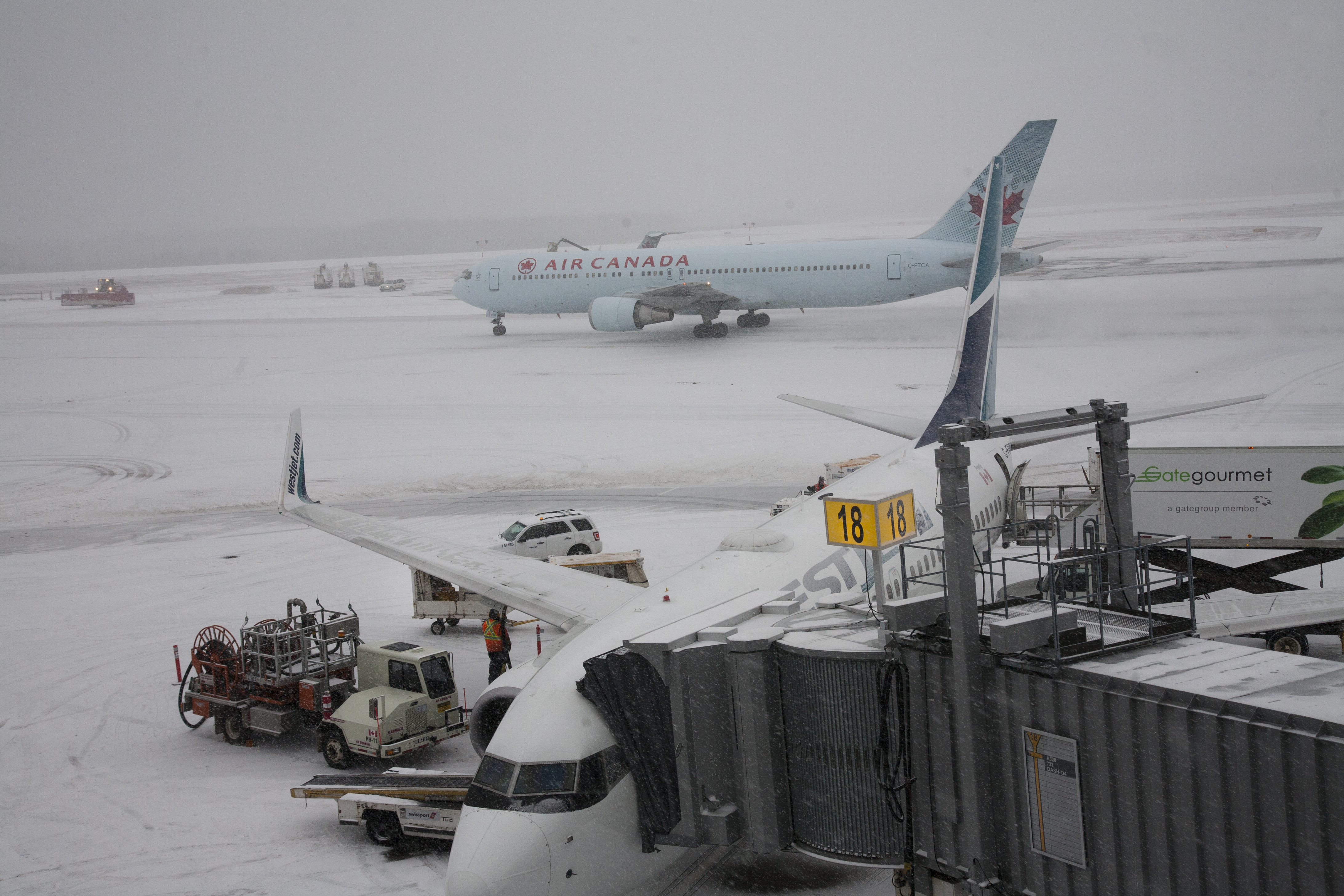 Crews at Halifax's Stanfield Airport ready a Westjet plane for it's next flight as an Air Canada plane makes it way to the gate on a snowy day. Friday January 6, 2017 (Mike Harvey)