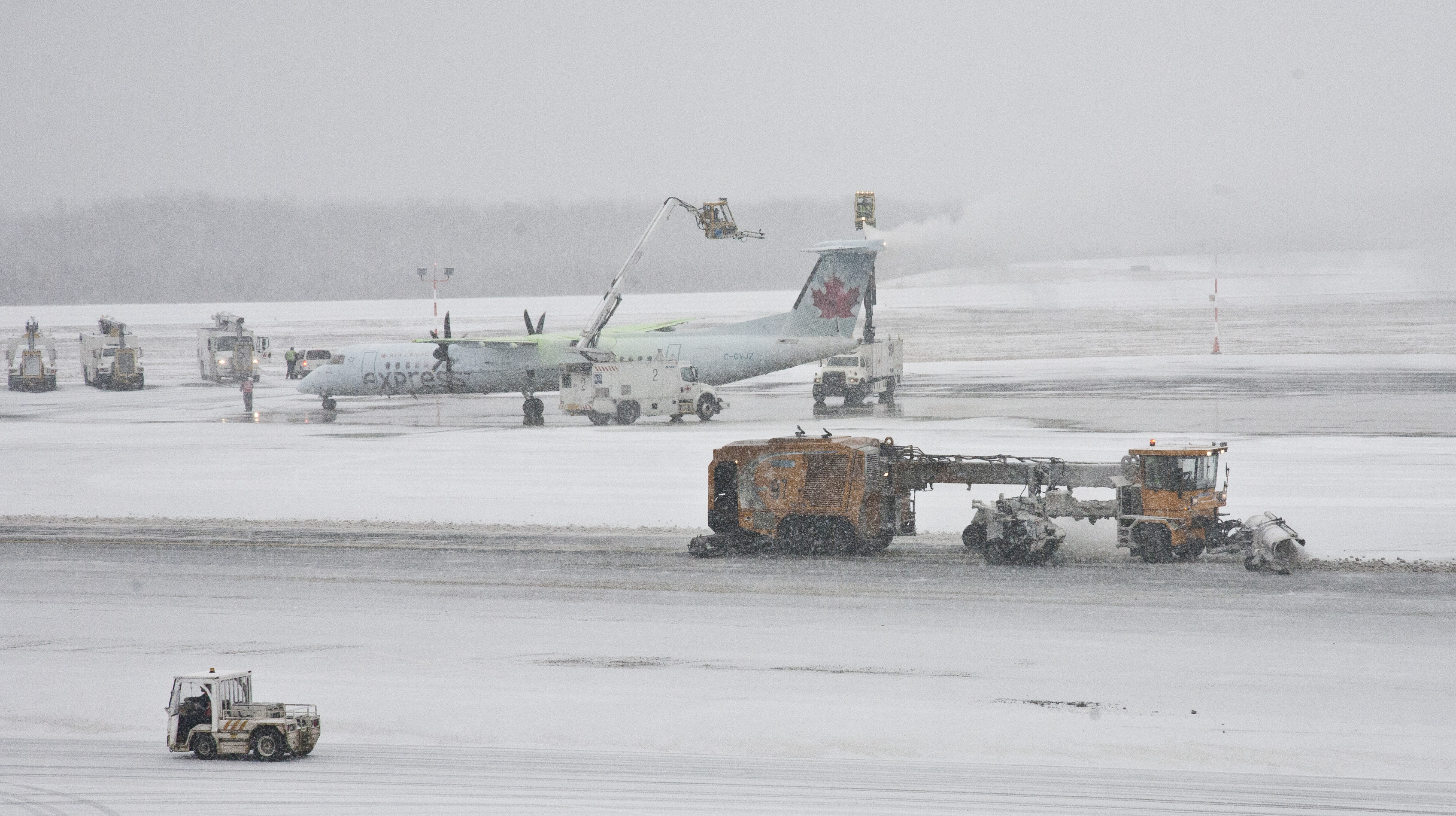 An Air Canada Express plane gets de-iced while a plow clears snow on the taramac at Halifax's Stanfield airport on a snowy Friday. Friday January 6, 2017. (Mike Harvey)