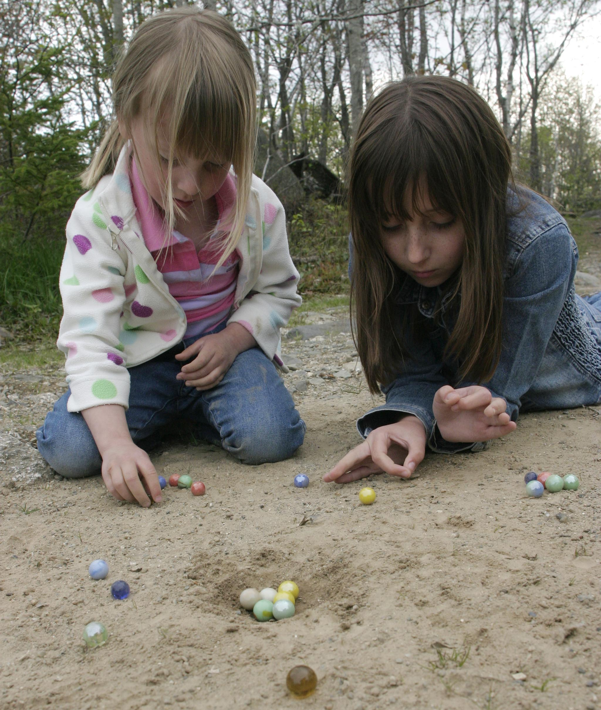 """Kids playing marbles, this game is called """"Bun Hole"""" , you try to got your marble as close to the hole as possible with outgoing in."""