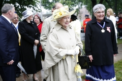 After arriving at the Halifax Commons, Queen Elizabeth walks with Sister Dorothy Moore to the Mi'kmaq cultural event where she met other elders and was presented with a painting by artist Alan Syliboy.