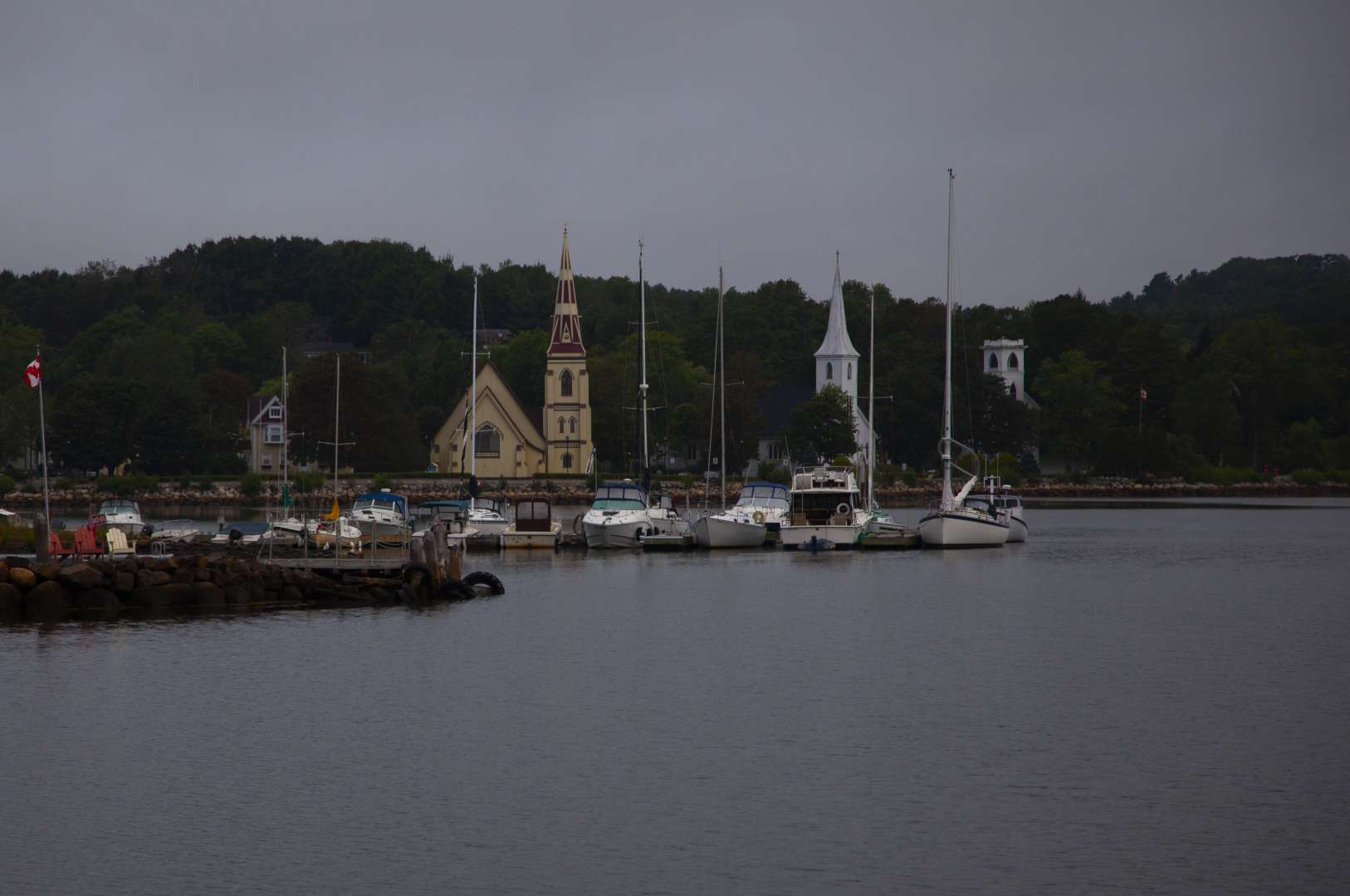 The Steeples of the Mahone Bay churches can be seen between Canadian Falgs on the waterfron in Mahone Bay, Nova Scotia